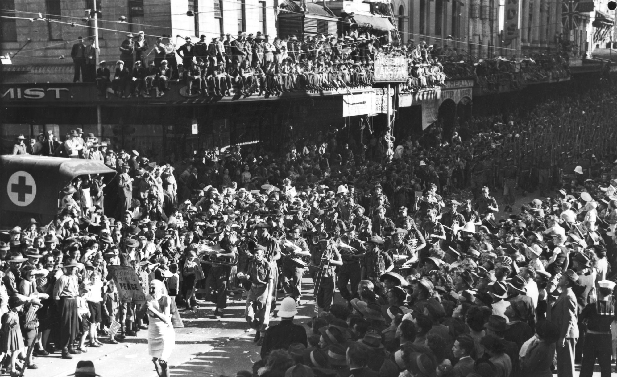 Army band leads a procession of soldiers on VJ Day in Brisbane, 1945
