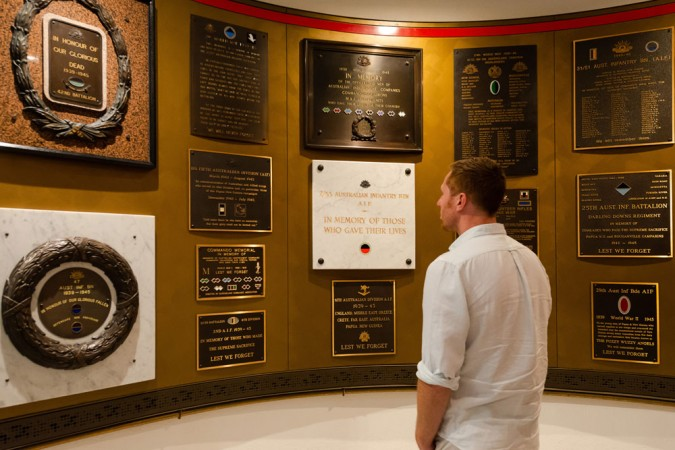 Man standing in World War II gallery looking at plaques on wall