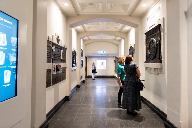 Lady with guide looking at wall plaque in World War I gallery