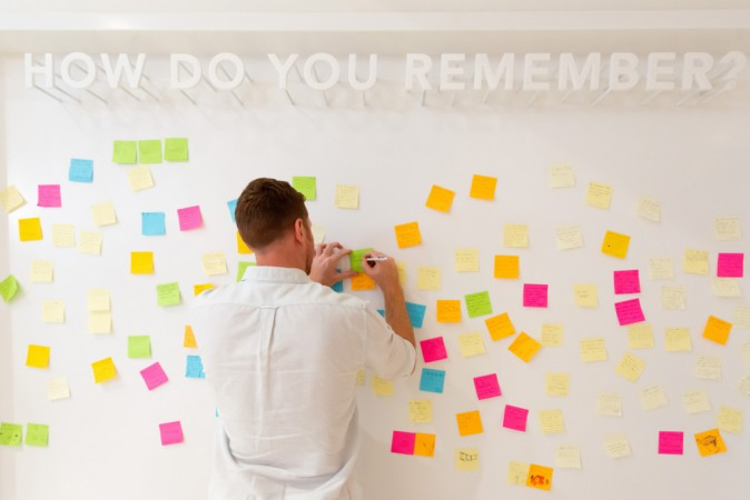 Man writing on wall of post it notes