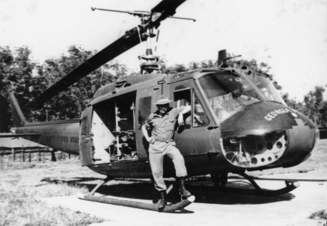 Corporal Victor Patty standing by a medivac Huey helicopter, Vietnam 1967