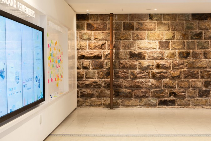 Sandstone wall by post it notes and Queensland Remembers screen