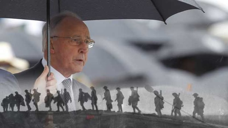 Man with umbrella at Remembrance Day ceremony