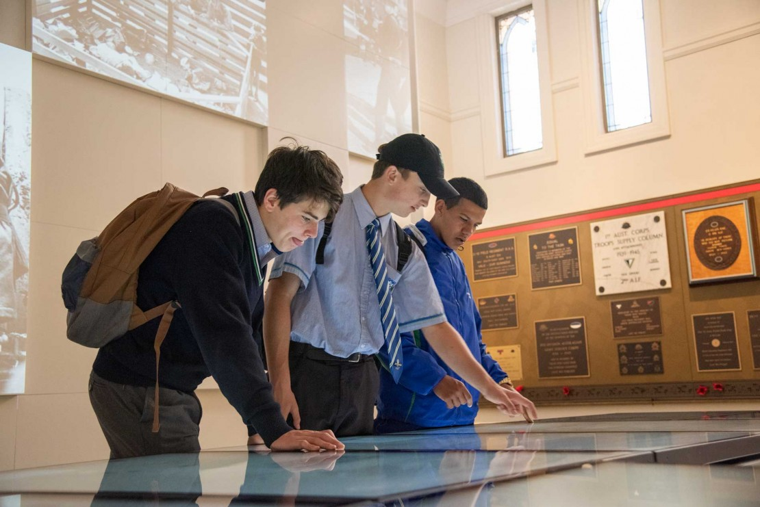 Students using touchscreen finding information Anzac Square