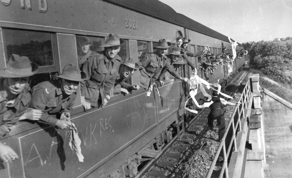 Soldiers waving from the window of a train in Brisbane, Queensland, 1940