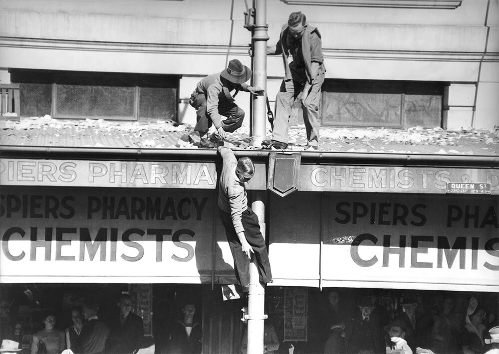 Young men attempt to reach a higher vantage point on VJ Day, Brisbane, 1945